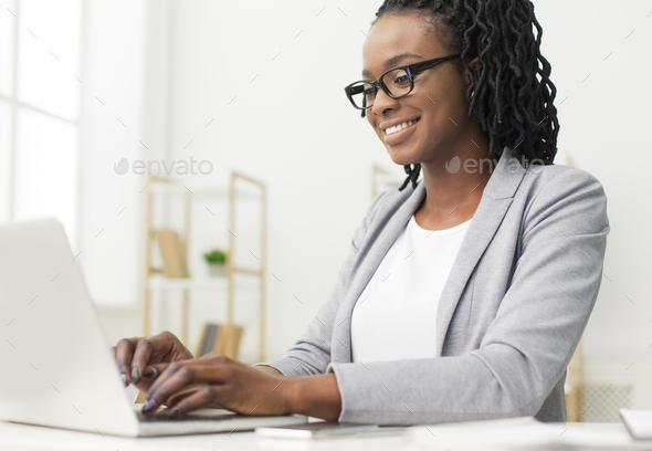 Smiling Office Manager Working On Laptop Sitting At Workplace - Stock Photo - Images