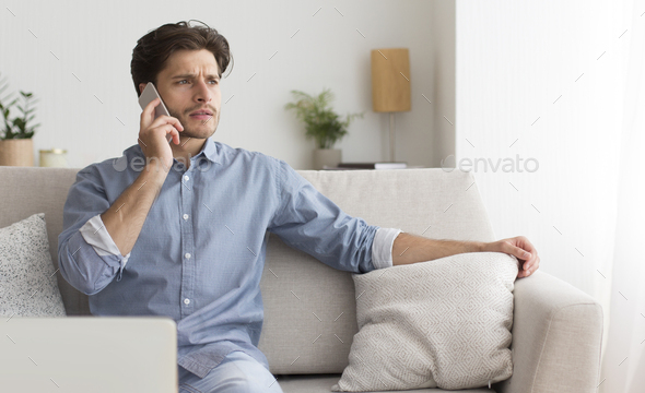 Businessman Talking On Cellphone Sitting At Laptop On Couch Indoor - Stock Photo - Images