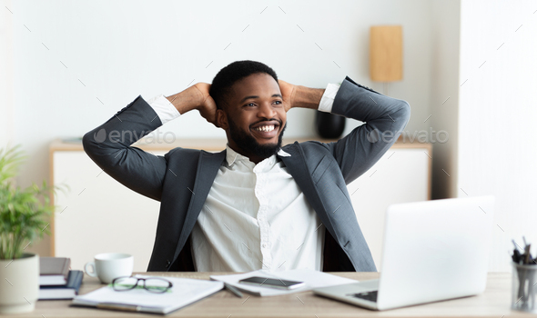 Black businessman relaxing at workplace, leaning back in chair - Stock Photo - Images