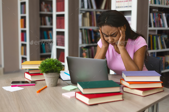 Tired afro girl stucked with laptop and books at library - Stock Photo - Images