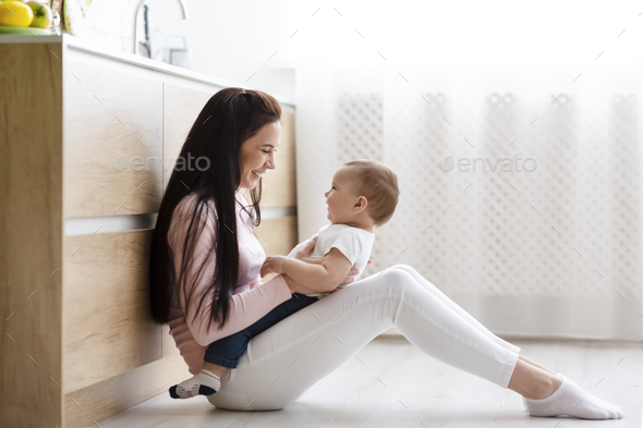 Happy mother tickling her cute baby son on kitchen floor - Stock Photo - Images