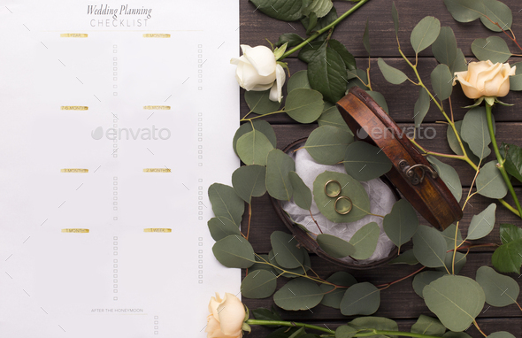 Wedding rings and paper planning checklist on wooden table - Stock Photo - Images