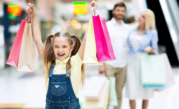 Little Girl Holding Bags Walking With Parents In Shopping Mall - Stock Photo - Images