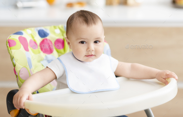 Cute baby boy sitting in high children chair in kitchen - Stock Photo - Images