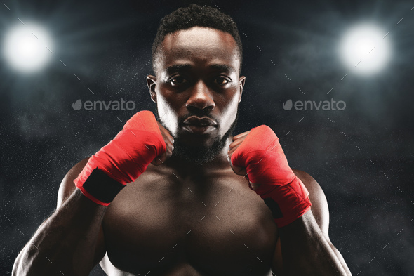 Concentrated fighter standing in defence pose on boxing ring - Stock Photo - Images