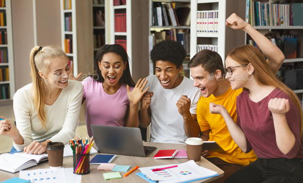Group of young happy students enjoying test results in library - Stock Photo - Images