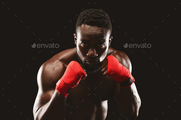 Professional fighter in boxing stance posing over black studio background - Stock Photo - Images