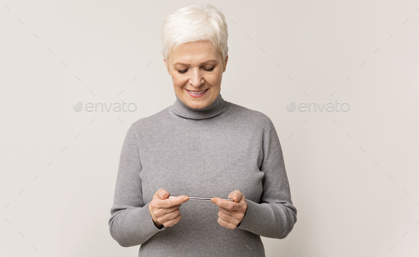 Senior woman playing video game on mobile phone and smiling - Stock Photo - Images