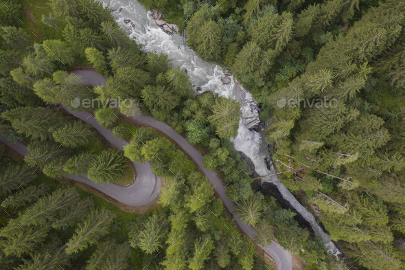 aerial view of a waterfall and a mountain road winding through a fir forest - Stock Photo - Images