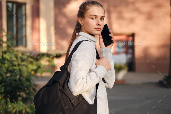 Student girl in sweater with backpack confidently looking in camera talking on cellphone outdoor - Stock Photo - Images