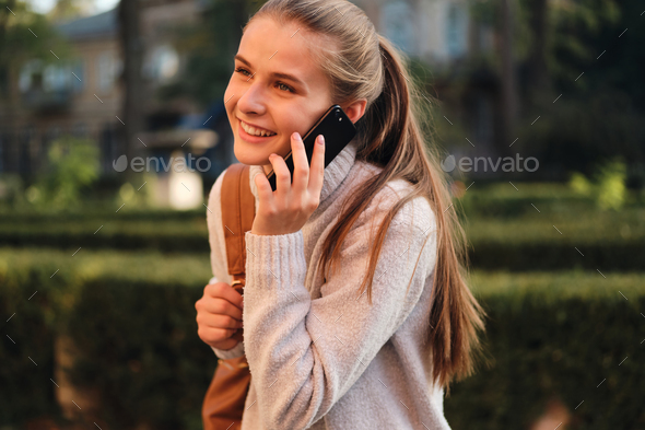 Young cheerful student girl in cozy sweater with backpack happily talking on cellphone outdoor - Stock Photo - Images