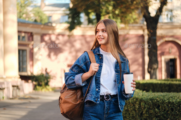 Pretty smiling student girl in denim jacket with backpack and coffee on study break in college - Stock Photo - Images