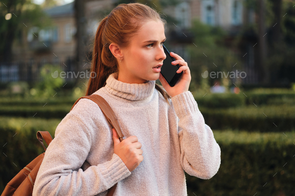 Young serious student girl in cozy sweater with backpack talking on cellphone outdoor - Stock Photo - Images