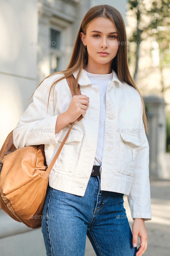 Attractive stylish student girl with backpack confidently looking in camera on city street - Stock Photo - Images