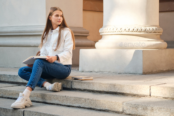 Attractive casual student girl thoughtfully studying with book on university stairs outdoor - Stock Photo - Images