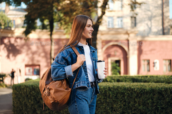 Student girl in denim jacket with backpack and coffee happily looking away in college campus outdoor - Stock Photo - Images