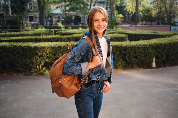 Beautiful smiling girl in denim jacket with stylish backpack joyfully looking in camera outdoor - Stock Photo - Images