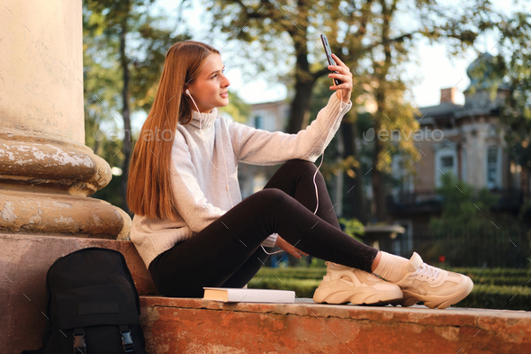 Attractive student girl in cozy sweater dreamily taking selfie during study break outdoor - Stock Photo - Images
