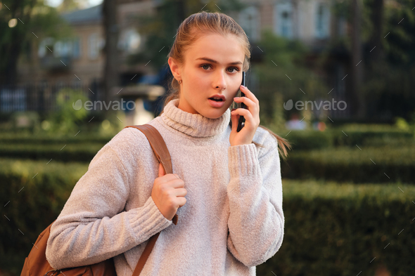 Astonished student girl in sweater with backpack talking on cellphone amazedly looking in camera - Stock Photo - Images