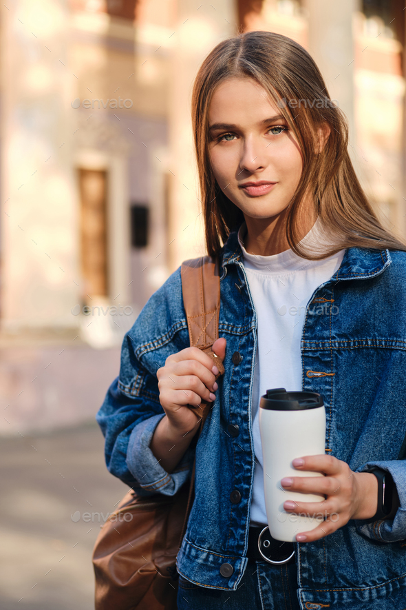 Pretty student girl in denim jacket with cup to go dreamily looking in camera in university outdoor - Stock Photo - Images
