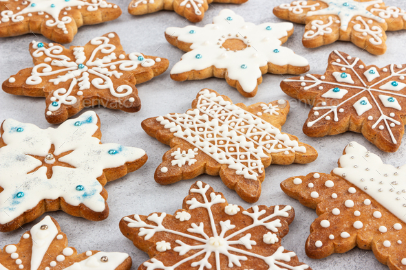 Christmas ginger cookies in the shape of snowflakes, decorated with various aisings - Stock Photo - Images
