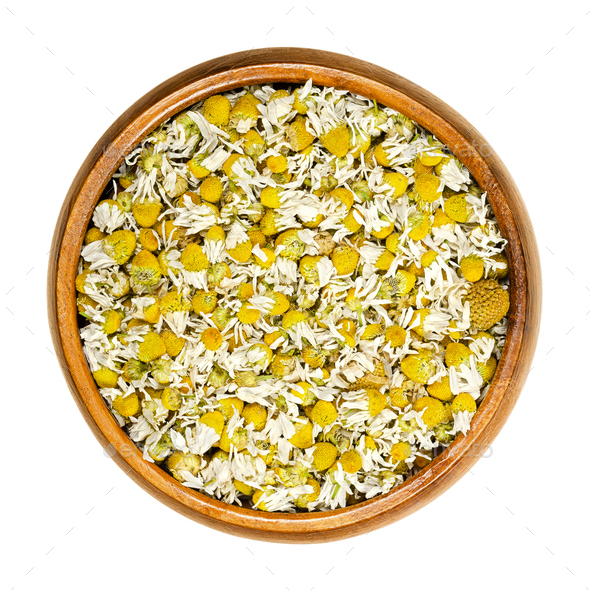 Dried chamomile blossoms, camomile tea in wooden bowl - Stock Photo - Images