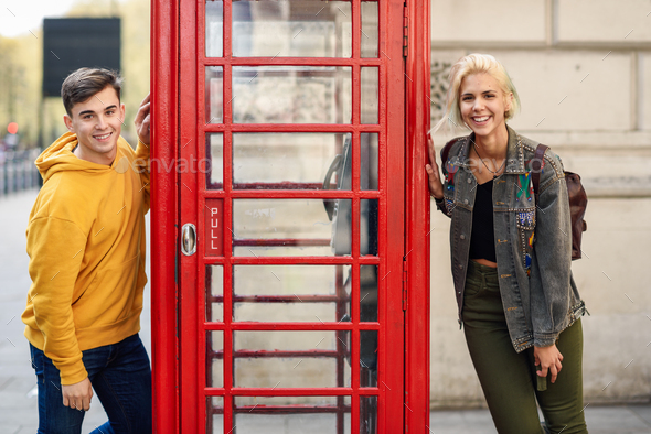 Young couple of friends near a classic British red phone booth - Stock Photo - Images