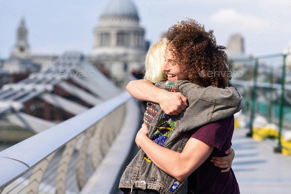 Happy couple hugging by Millennium bridge, River Thames, London - Stock Photo - Images