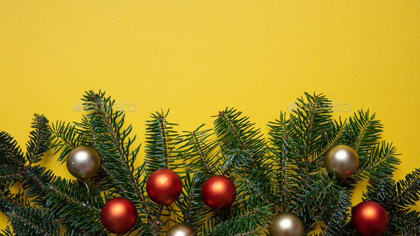 Fir twig fresh and christmas baubles against yellow color background - Stock Photo - Images