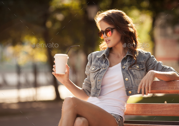 Young Woman Drinking Coffee From Paper Cup. Sitting On Bench - Stock Photo - Images