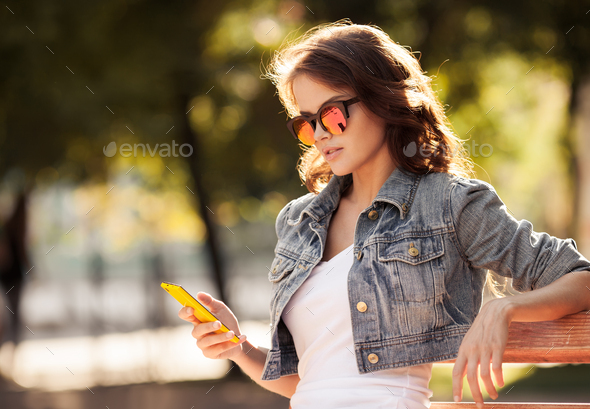 Young Woman Using Smartphone. City Park On Background. - Stock Photo - Images