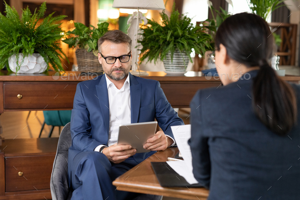 Middle aged entrepreneur with touchpad looking through online information - Stock Photo - Images