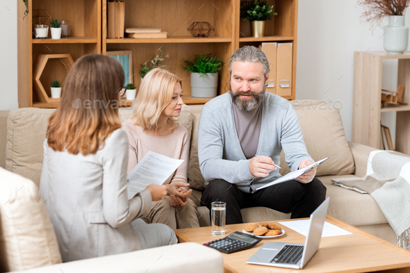 Bearded man looking through paper while consulting with real estate agent - Stock Photo - Images