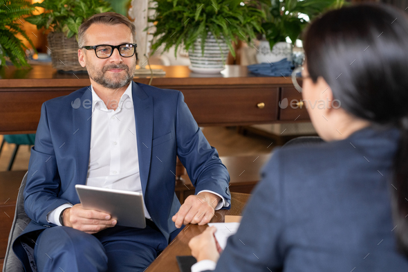 Well-dressed confident businessman with tablet sitting by table in restaurant - Stock Photo - Images