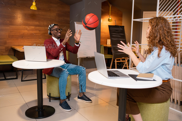 Two happy young multicultural students of college playing with ball in cafe - Stock Photo - Images