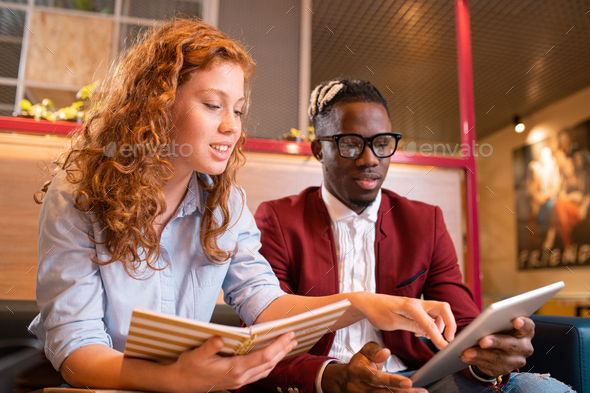 Young successful multicultural students or employees looking at touchpad display - Stock Photo - Images