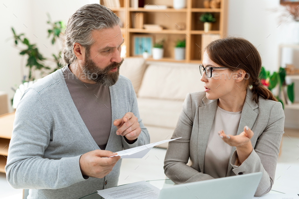 Mature client specifying details of contract while consulting with agent - Stock Photo - Images