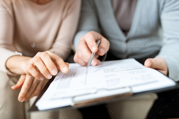 Human hands pointing at one of points of contract or other document - Stock Photo - Images
