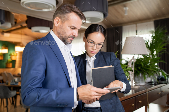 Two serious colleagues in formalwear reading electronic document in touchpad - Stock Photo - Images