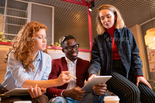 Three young successful colleagues in casualwear gathered for meeting in cafe - Stock Photo - Images