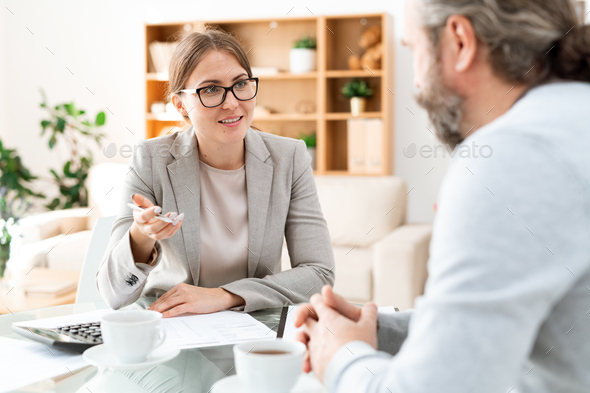 Happy accountant in formalwear looking at mature colleague during discussion - Stock Photo - Images