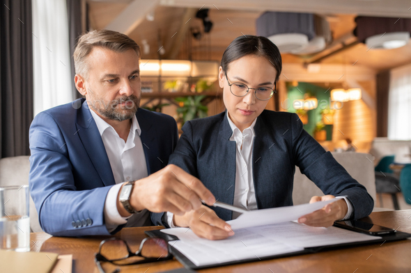 Serious young businesswoman looking through paper before signing it - Stock Photo - Images