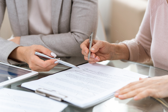 Two businesswomen consulting or discussing terms of contract at meeting - Stock Photo - Images