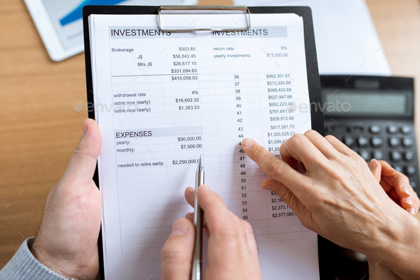 Overview of human hands over financial paper during discussion of expenses - Stock Photo - Images