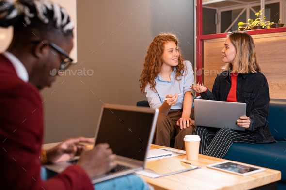 Two young happy casual businesswomen or students discussing working moments - Stock Photo - Images