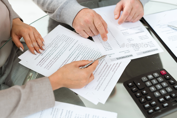 Hands of agent and mature man pointing at financial documents - Stock Photo - Images