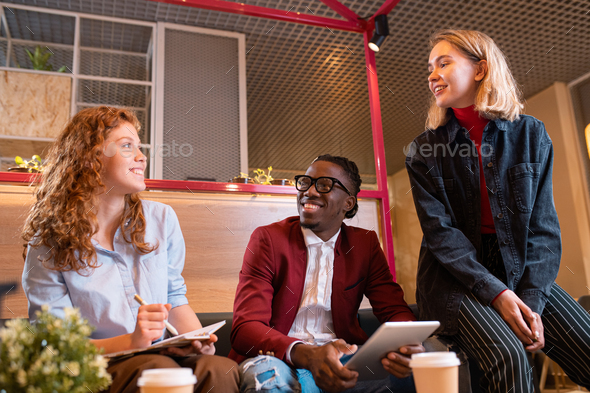 Three young cheerful managers discussing working questions at meeting - Stock Photo - Images