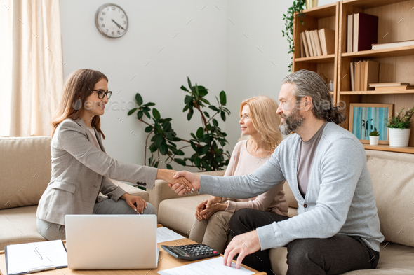 Casual bearded man shaking hand of young female real estate agent over desk - Stock Photo - Images