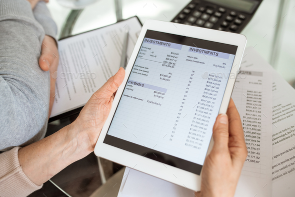 Hands of mature accountant holding touchpad with electronic financial document - Stock Photo - Images