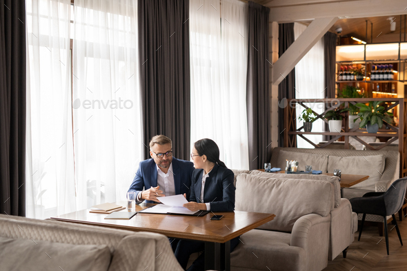 Two successful business partners discussing papers and consulting at meeting - Stock Photo - Images
